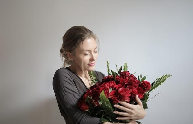 Junge schöne frau, die rote rosen hält
