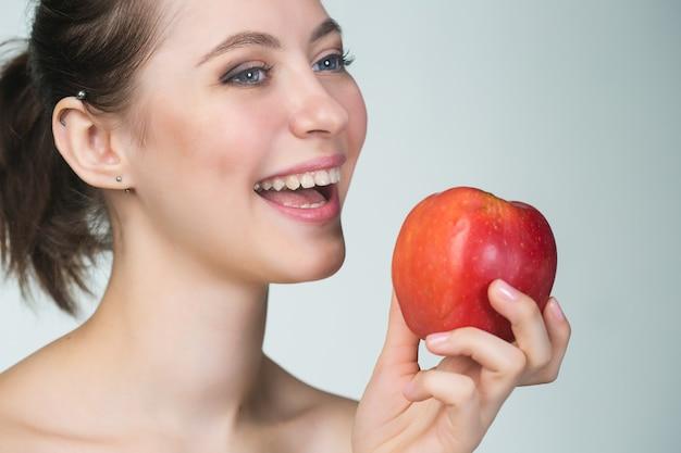 Junge schöne frau, die roten apfel isst