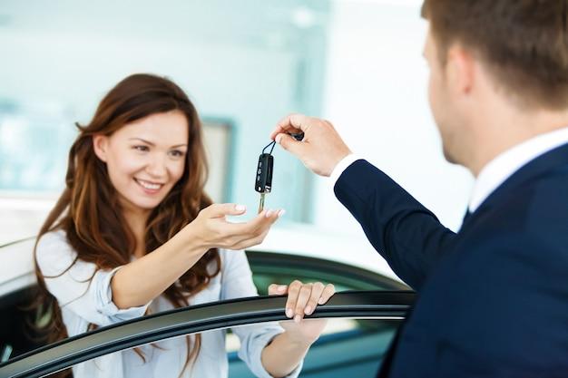 Junge schöne frau, die schlüssel beim sitzen am auto nimmt