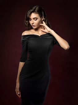 Junge schöne frau, die schwarzes abendkleid trägt, das über dunkelrotem hintergrund aufwirft