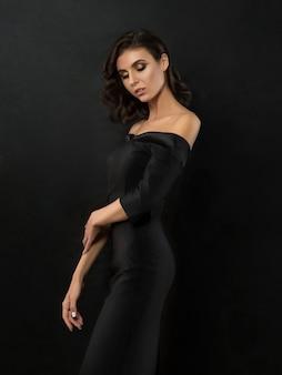 Junge schöne frau, die schwarzes abendkleid trägt, das über schwarzem hintergrund aufwirft