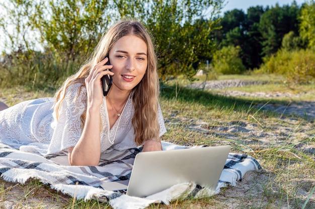 Junge schöne frau, die sich am strand sonnen, am telefon spricht und am computer arbeitet.