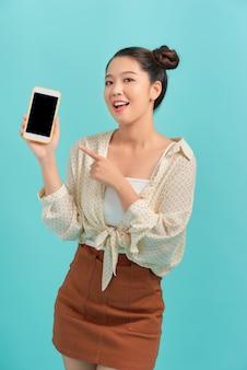 Junge schöne frau, die smartphone an der blauen wand hält