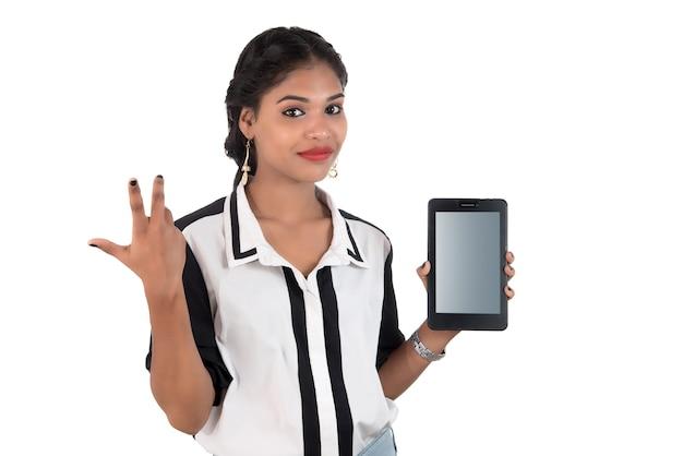 Junge schöne frau, die smartphone des leeren bildschirms auf weißem hintergrund hält