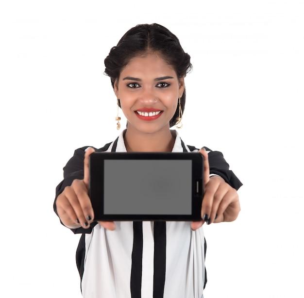 Junge schöne frau, die smartphone des leeren bildschirms auf weißem raum hält