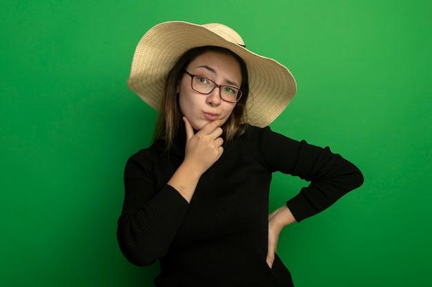 Junge schöne frau, die sommerhut in einem schwarzen rollkragenpullover und in den gläsern trägt, die beiseite mit skeptischem ausdruck mit hand auf kinn denken, das über grüner wand steht