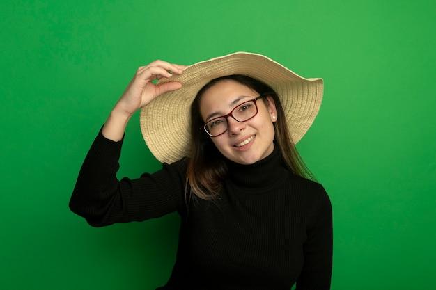 Junge schöne frau, die sommerhut in einem schwarzen rollkragenpullover und in den gläsern trägt, die vorne glücklich und positiv stehen über grüner wand stehen