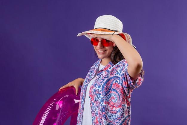 Junge schöne frau, die sommerhut und rote sonnenbrille hält aufblasbaren ring, der weit weg mit der hand schaut, um etwas lächelndes und glückliches, bereites feiertagskonzept über lila zu schauen
