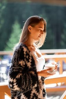 Junge schöne frau, die tasse kaffeemorgen hält. glückliches fröhliches entspannendes, barista-konzeptbanner. mädchen im übergroßen hemd machen pause zu hause