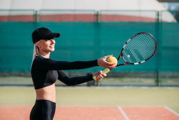 Junge schöne frau, die tennis auf einem gericht spielt. gesunder sportlebensstil