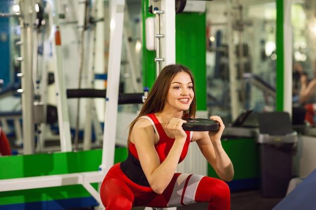 Junge schöne frau, die übungen mit dummkopf in der gymnastik tut. frohes lächelndes mädchen genießt mit ihrem trainingsprozeß