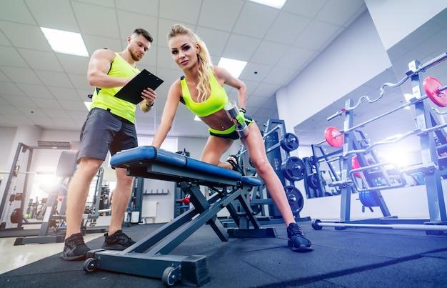 Junge schöne frau, die übungen mit personal trainer im fitnessstudio macht. gesundheitskonzept. hantel heben.