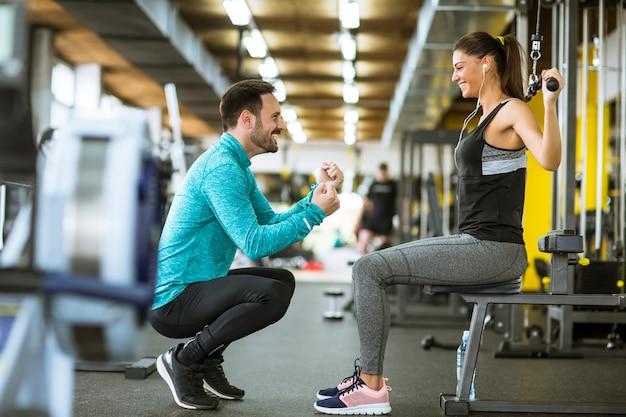 Junge schöne frau, die übungen mit personal trainer macht