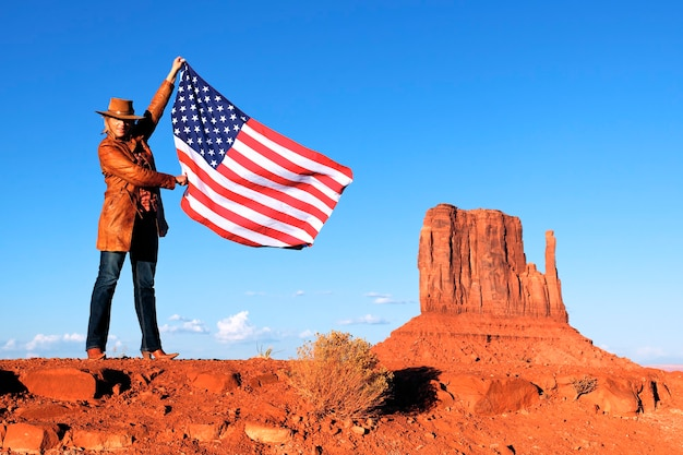 Junge schöne frau, die usa-flagge am monument valley hält