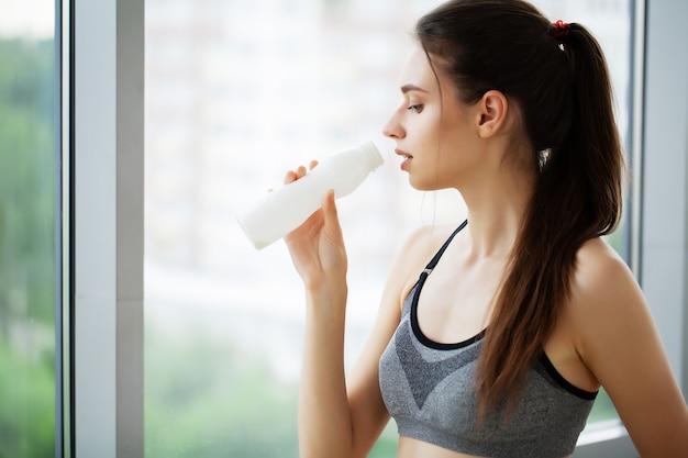 Junge schöne frau, die von plastikflasche joghurt trinkt