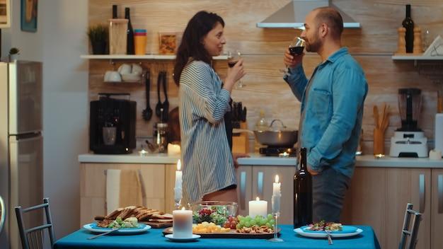 Junge schöne frau, die während des festlichen abendessens flirtet. erwachsenes paar mit romantischem date zu hause, in der küche, rotwein trinken, reden, lächeln, das essen im esszimmer genießen.
