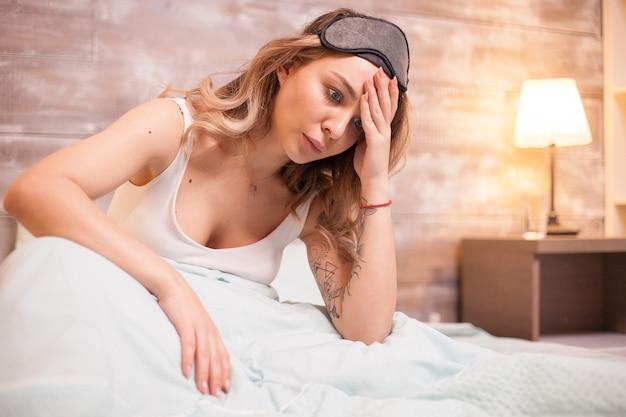 Junge schöne frau, die während ihres schlafes nach einem albtraum leidet.