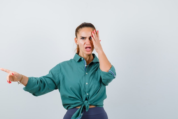Junge schöne frau, die weg zeigt, während sie die hand im grünen hemd hält und wütend aussieht, vorderansicht.