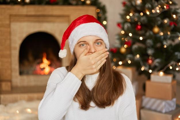 Junge schöne frau, die weihnachtsmannhut und weißen pullover trägt, der zu hause um weihnachtsdekoration ist