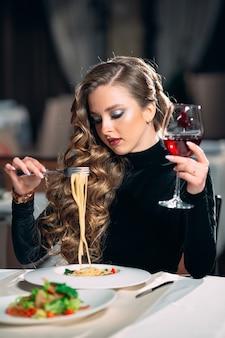 Junge schöne frau, die wein in einem restaurant trinkt