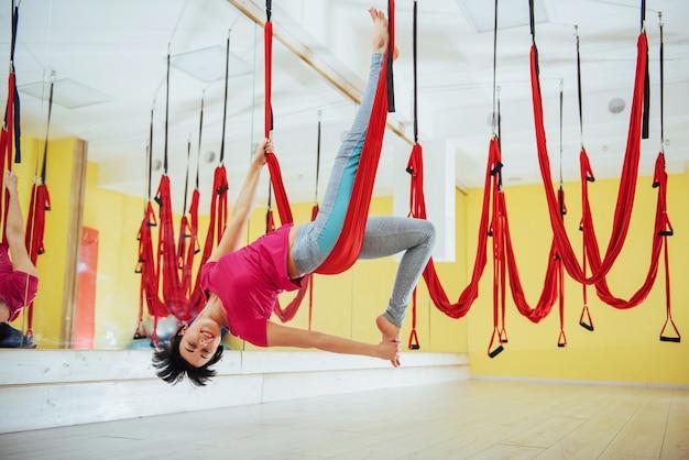 Junge schöne frau, die yoga-fliege mit einer hängematte im hellen studio praktiziert. das konzept der geistigen und körperlichen gesundheit.