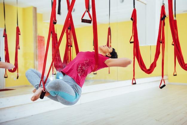 Junge schöne frau, die yoga-fliege mit einer hängematte im hellen studio praktiziert. fliegen, fitness, dehnung, gleichgewicht, bewegung.
