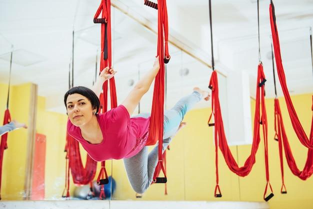 Junge schöne frau, die yoga-fliege mit einer hängematte praktiziert, das konzept der geistigen und körperlichen gesundheit.