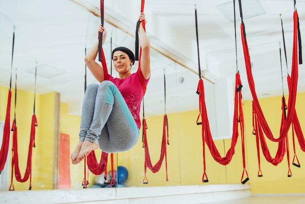 Junge schöne frau, die yoga-fliege mit einer hängematte praktiziert. fliegen, fitness, dehnung, gleichgewicht, bewegung.