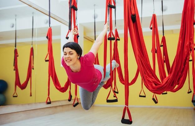 Junge schöne frau, die yoga-fliege mit einer hängematte praktiziert