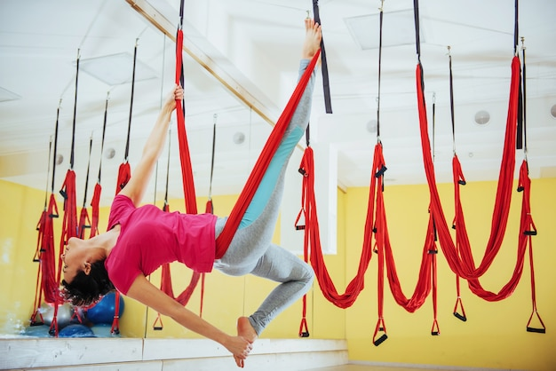 Junge schöne frau, die yoga fly mit einer hängematte im studio praktiziert.