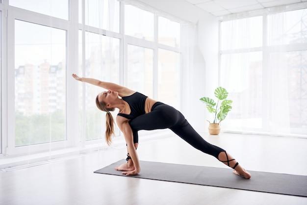 Junge schöne frau, die yoga in einem modernen hellen raum mit großen fenstern tut. yoga zu hause konzept.