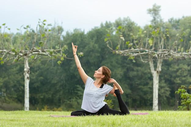 Junge schöne frau, die yogaübung im freien tut