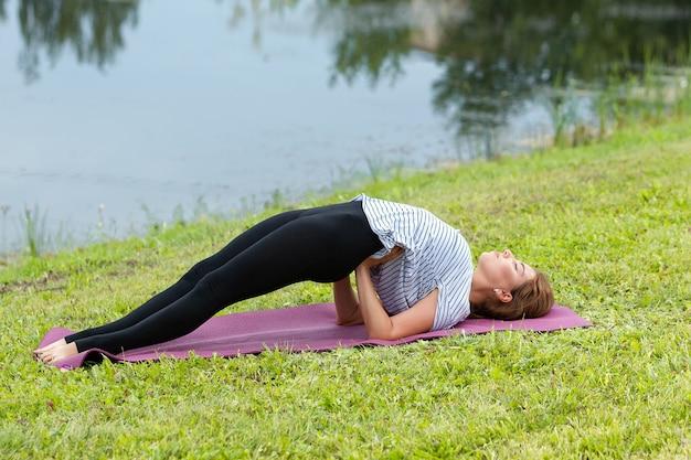 Junge schöne frau, die yogaübung im grünen park tut. gesundes lebensstil- und fitnesskonzept.