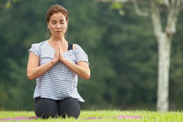 Junge schöne frau, die yogaübung im grünen park tut