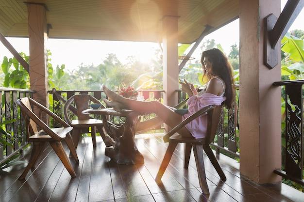Junge schöne frau, die zellintelligentes telefon sitzt, sitzen auf terrasse