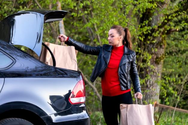 Junge schöne frau, die zum auto mit einkäufen vom einkaufszentrum geht