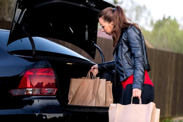 Junge schöne frau, die zum auto mit einkäufen vom supermarkt geht