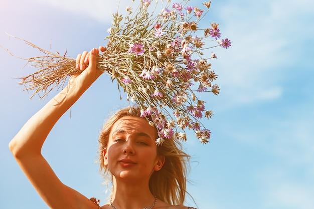 Junge schöne frau, die zur sonne lächelt und einen strauß wildblumen über ihrem kopf hält