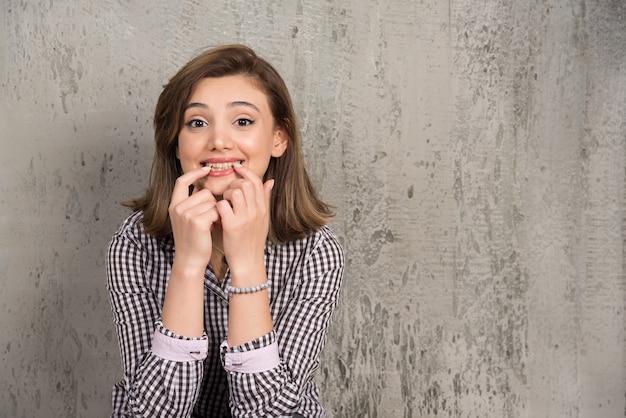 Junge schöne frau, die zuversichtlich zeigt und mit den fingern zähnen und mund zeigt