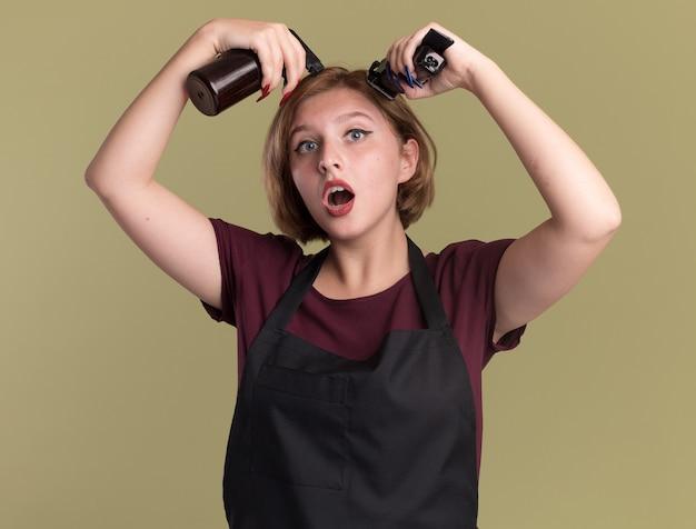Junge schöne frau friseur in der schürze, die sprühflasche und trimmermaschine hält, die versuchen, ihr haar zu schneiden, das über grüner wand steht
