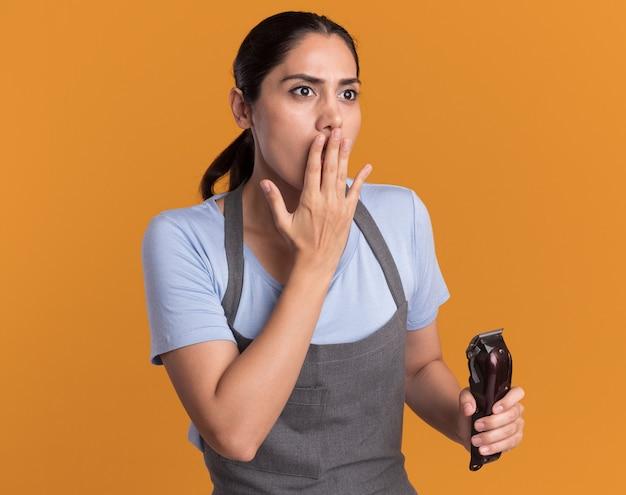 Junge schöne frau friseur in der schürze hält trimmer, der beiseite erstaunt und überrascht bedeckt mund mit hand über orange wand schaut