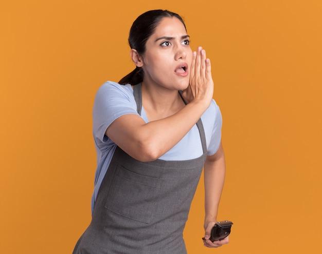 Junge schöne frau friseur in der schürze hält trimmer, der mit hand nahe mund flüstert, der zuversichtlich über orange wand schaut