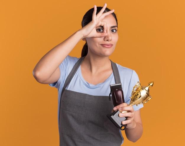 Junge schöne frau friseur in der schürze hält trimmer und goldtrophäe, die vorne lächelnd zeigt, ok zeichen zeigend, das über orange wand steht