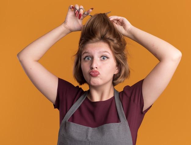 Junge schöne frau friseurin in der schürze, die versucht, ihr haar mit einer schere zu schneiden, die verwirrt und überrascht über orange wand steht