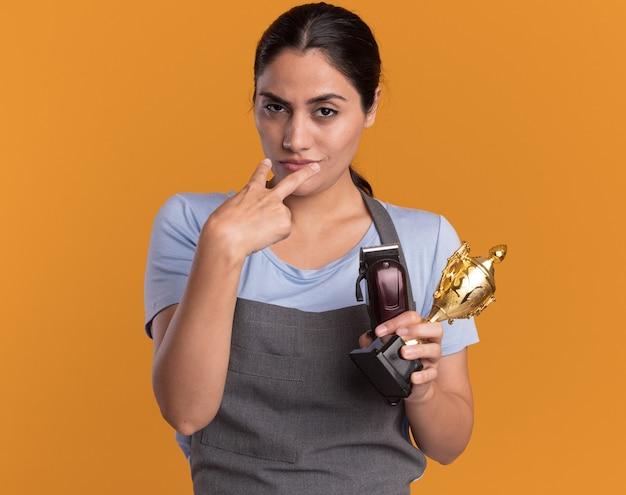 Junge schöne frau friseurin in der schürze hält trimmer und goldtrophäe und schaut selbstbewusst mit den fingern auf ihre augen, wodurch sie beobachten, wie sie über eine orangefarbene wand stehen