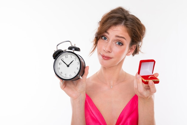 Junge schöne frau hält einen kasten für einen verlobungsring und einen wecker