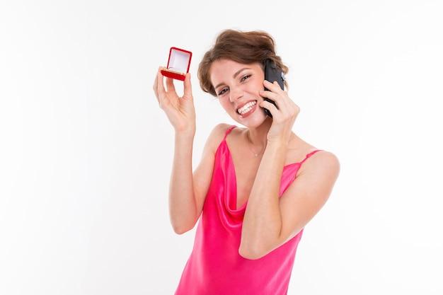 Junge schöne frau hält einen kasten für einen verlobungsring und ruft das telefon jemand an