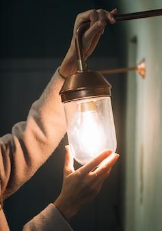 Junge schöne frau hält in der hand eine kleine wandlampe