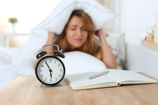 Junge schöne frau hasst es, früh am morgen aufzuwachen. schläfriges mädchen, das wecker betrachtet und versucht, sich unter dem kissen zu verstecken