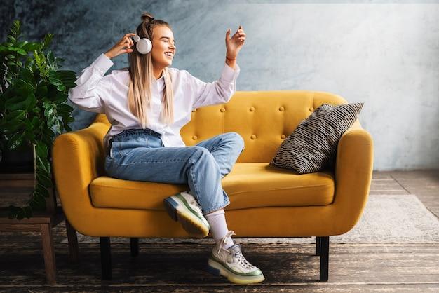 Junge schöne frau hört musik mit kopfhörern, während sie auf dem sofa im raum sitzt.